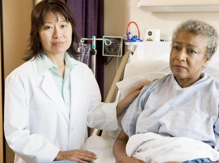 woman in hospital bed with doctor beside her