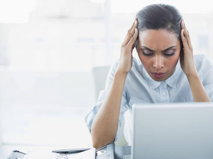 woman with hands to her head looking at laptop