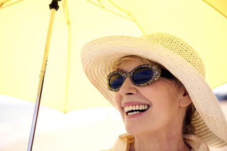 A smiling woman with a sun hat and umbrella.