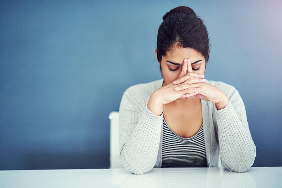 Mujer estresada con las manos cubriéndose el rostro